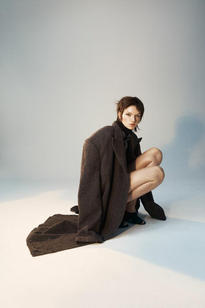 Modellen har på sig kappa och skor från Balenciaga