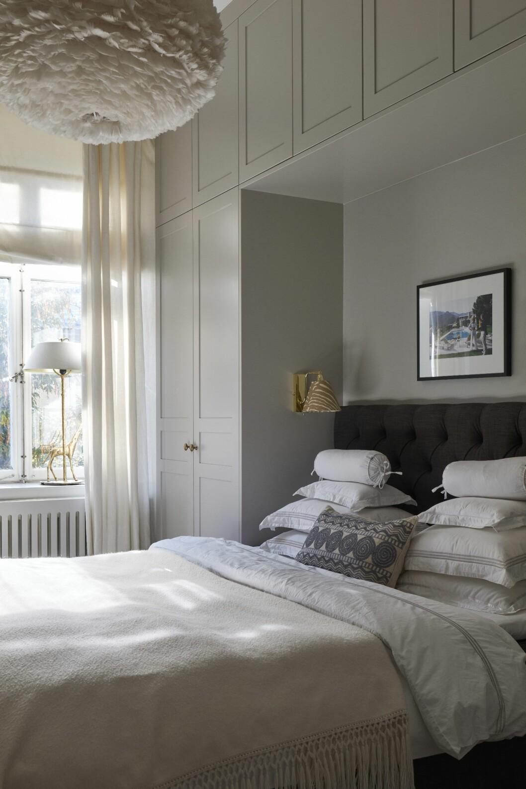 platsbyggd compact living-garderob runt sängen i sovrummet