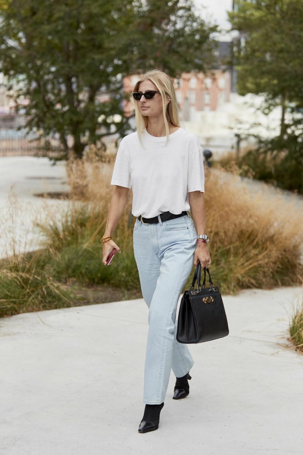 Bär den vita t-shirten till ljusa jeans och svarta accessoarer för en klassisk look.