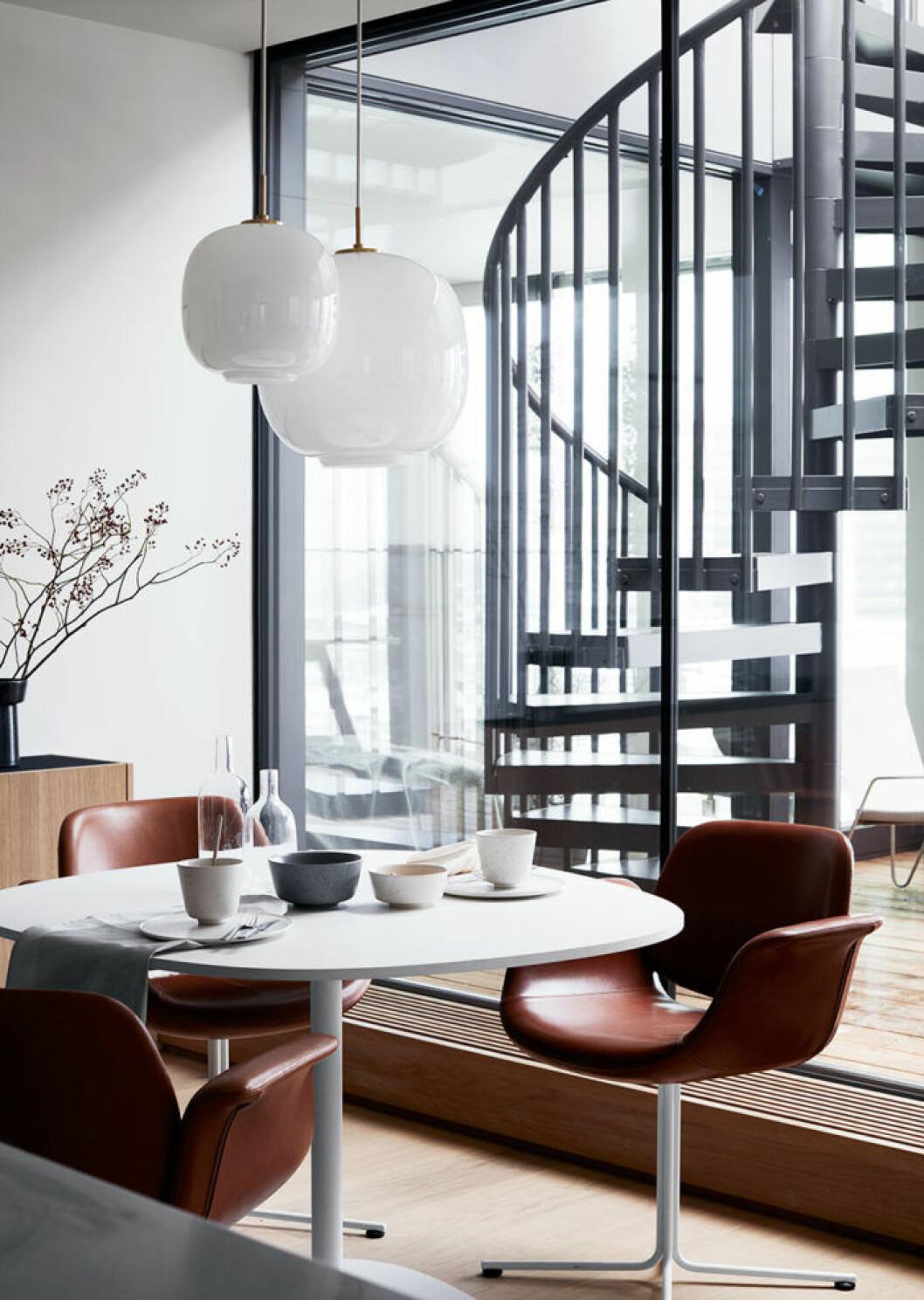 Bekväm matplats med bord och stolar från Erik Jørgensen. Keramiken Ombria kommer från Kähler, bestick från Kay Bojesen och bordslinne från Georg Jensen Damask. I bakgrunden skymtar  den skulpturala spiraltrappan som leder upp till takterrassen.