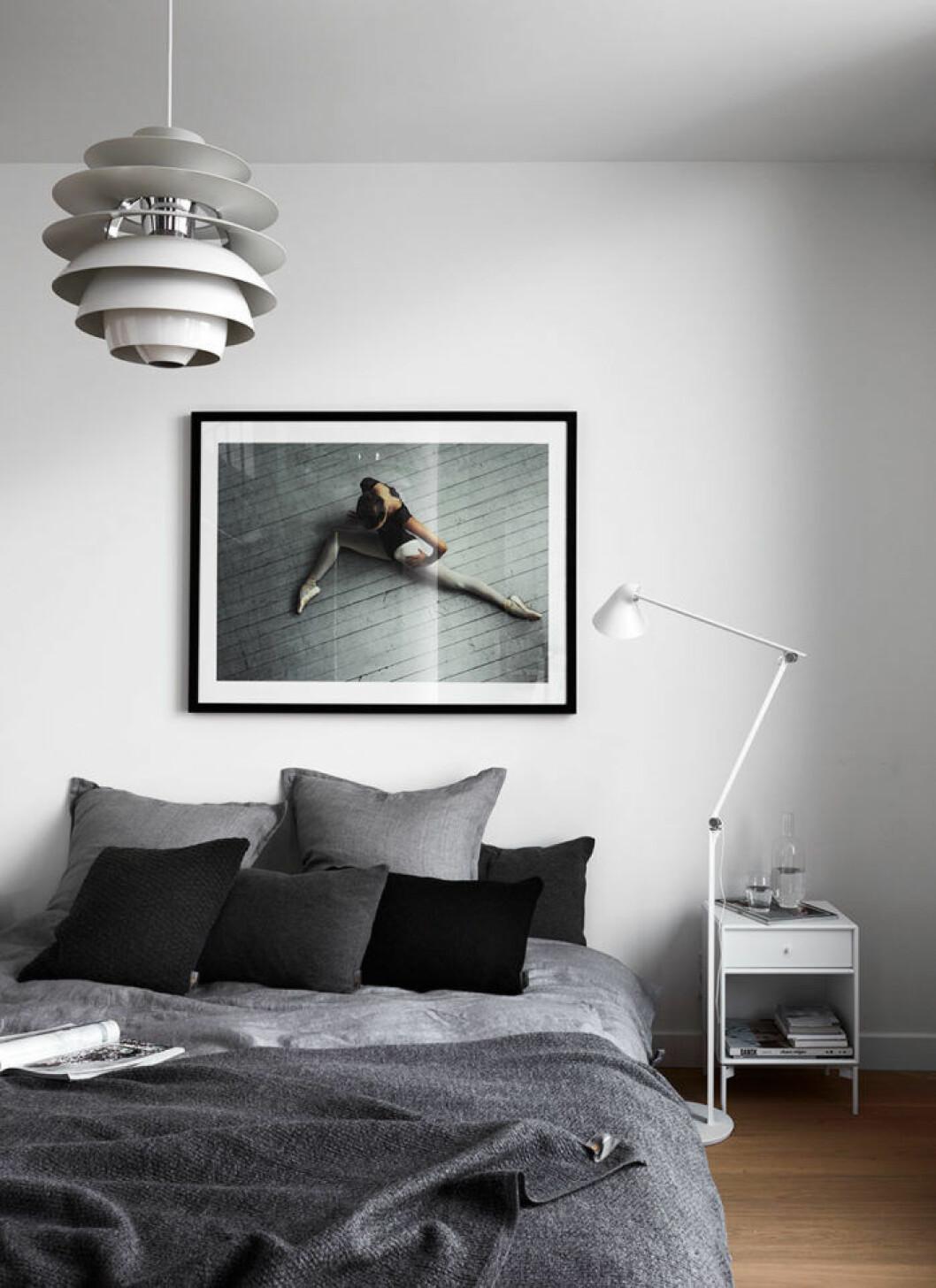Avskalat och stillsamt i sovrummet. Fotokonst Ballerina av Max Modén. Sänglinne och stickade plädar från Georg Jensen Damask. Lampor från Louis Poulsen och sängbord från Montana.