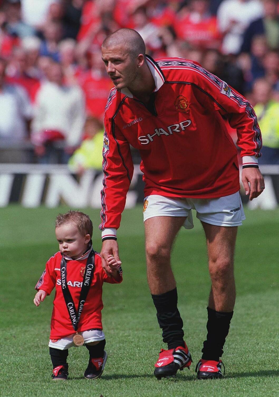 David Beckham håller lilla Brooklyn Beckham i handen