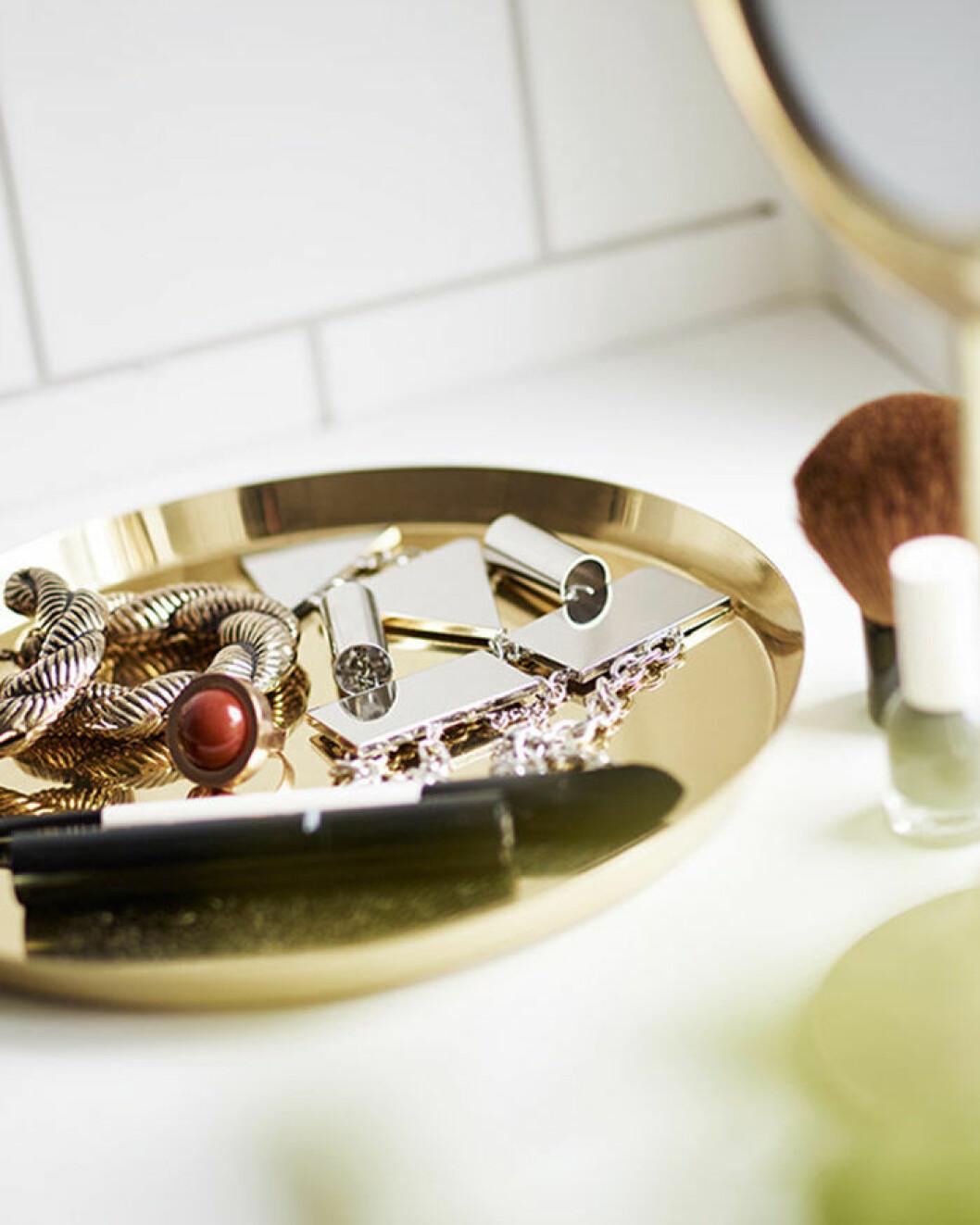 Bricka i mässing med smycken i badrummet