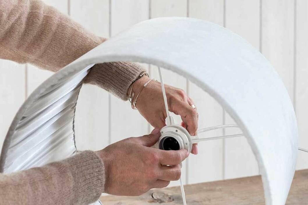 Ringfästet skruvas på lamphållaren