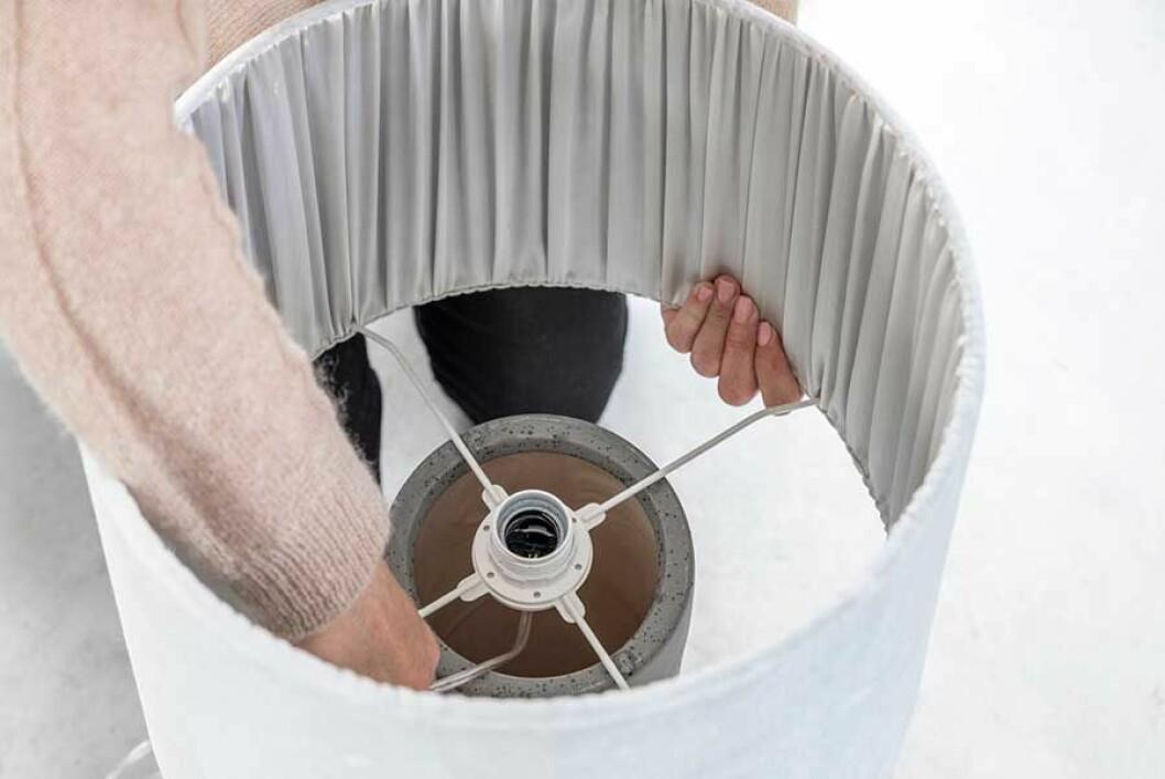 Lamphållaren placeras i ringen på lampskärmen och det andra ringfästet skruvas fast så att lampsladden sitter på plats