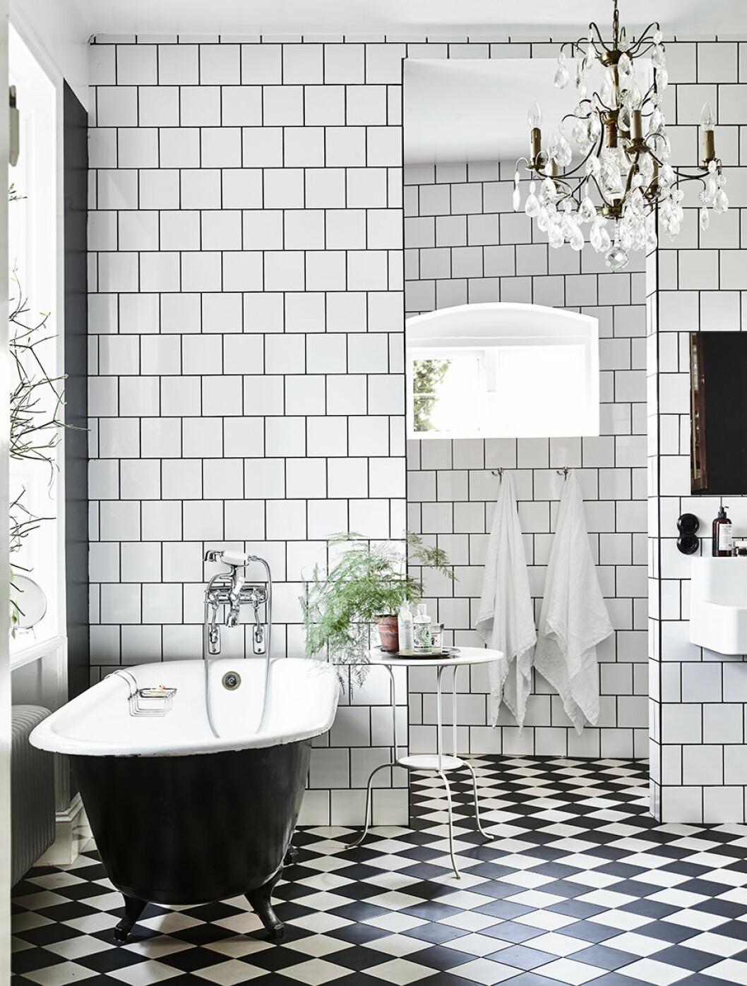 Svart badkar i badrum med vit och svart-rutigt klinkergolv