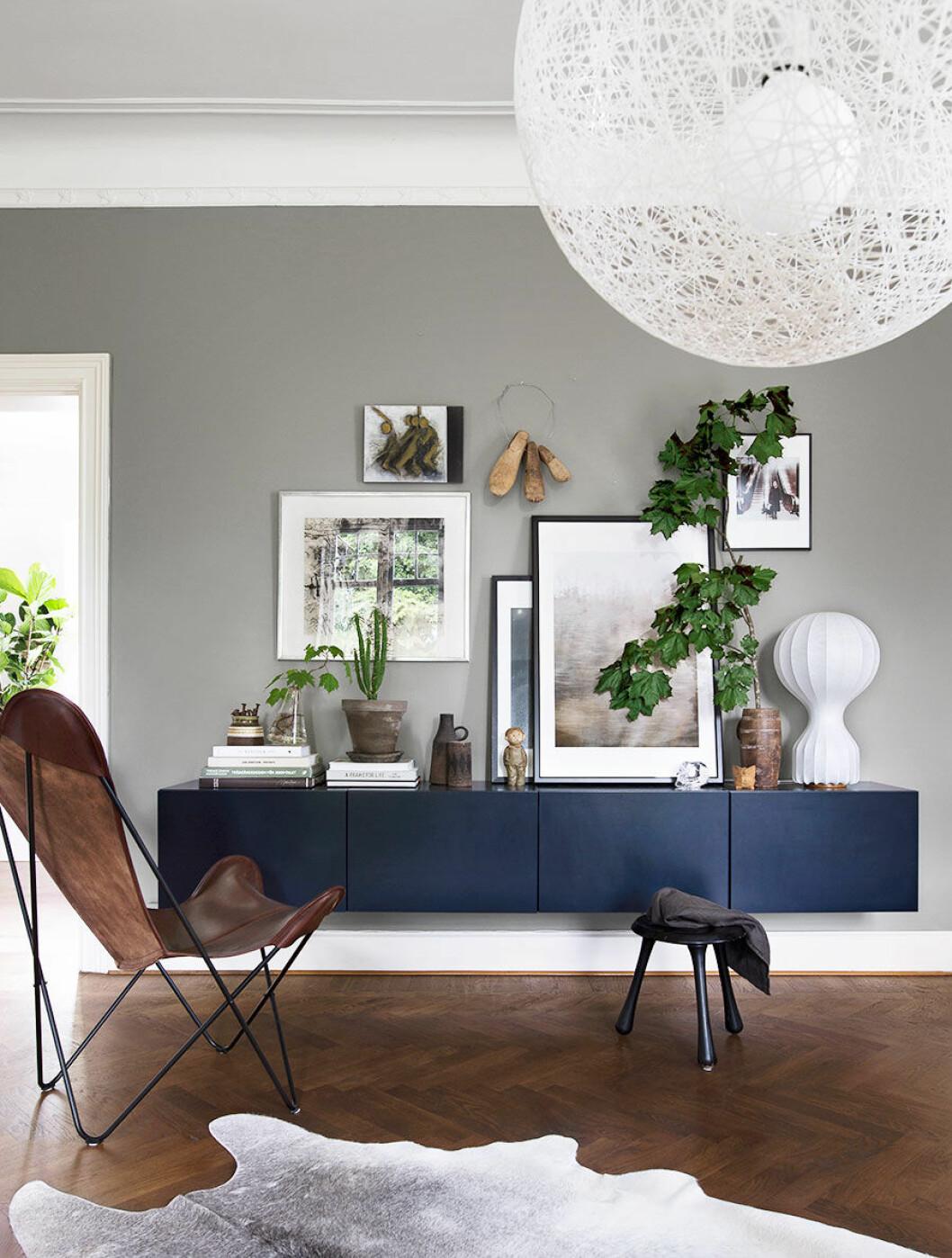 Gråmålat vardagsrum med stor lampa i vitt