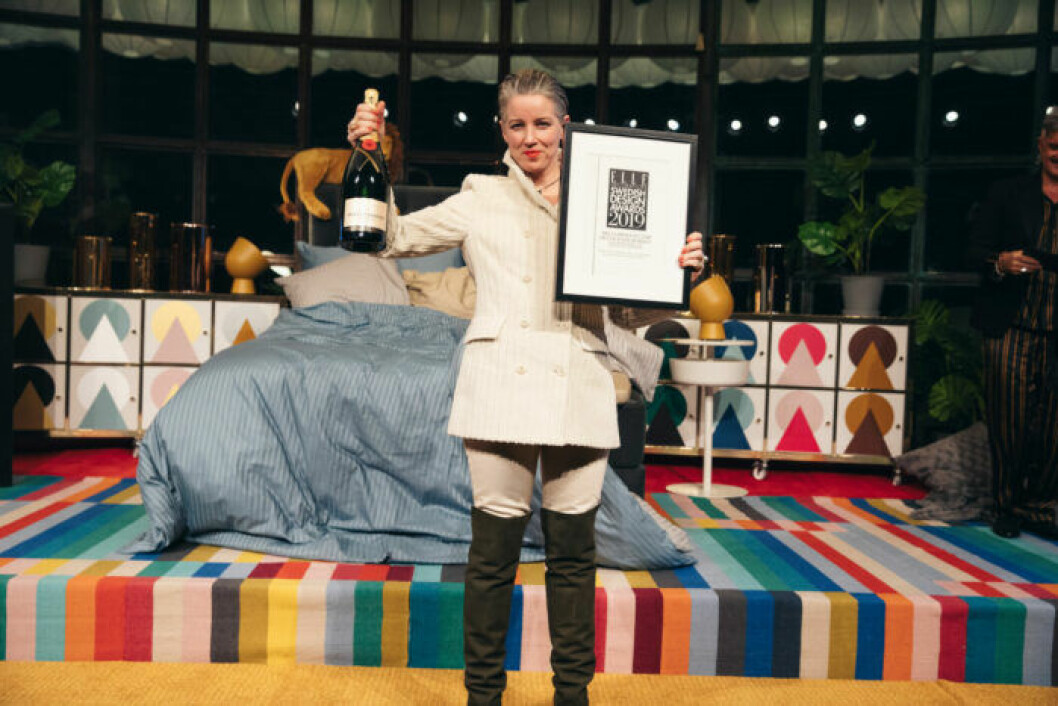 Glad vinnare på scen iklädd vit outfit på ELLE Decoration Swedish Design Awards 2019