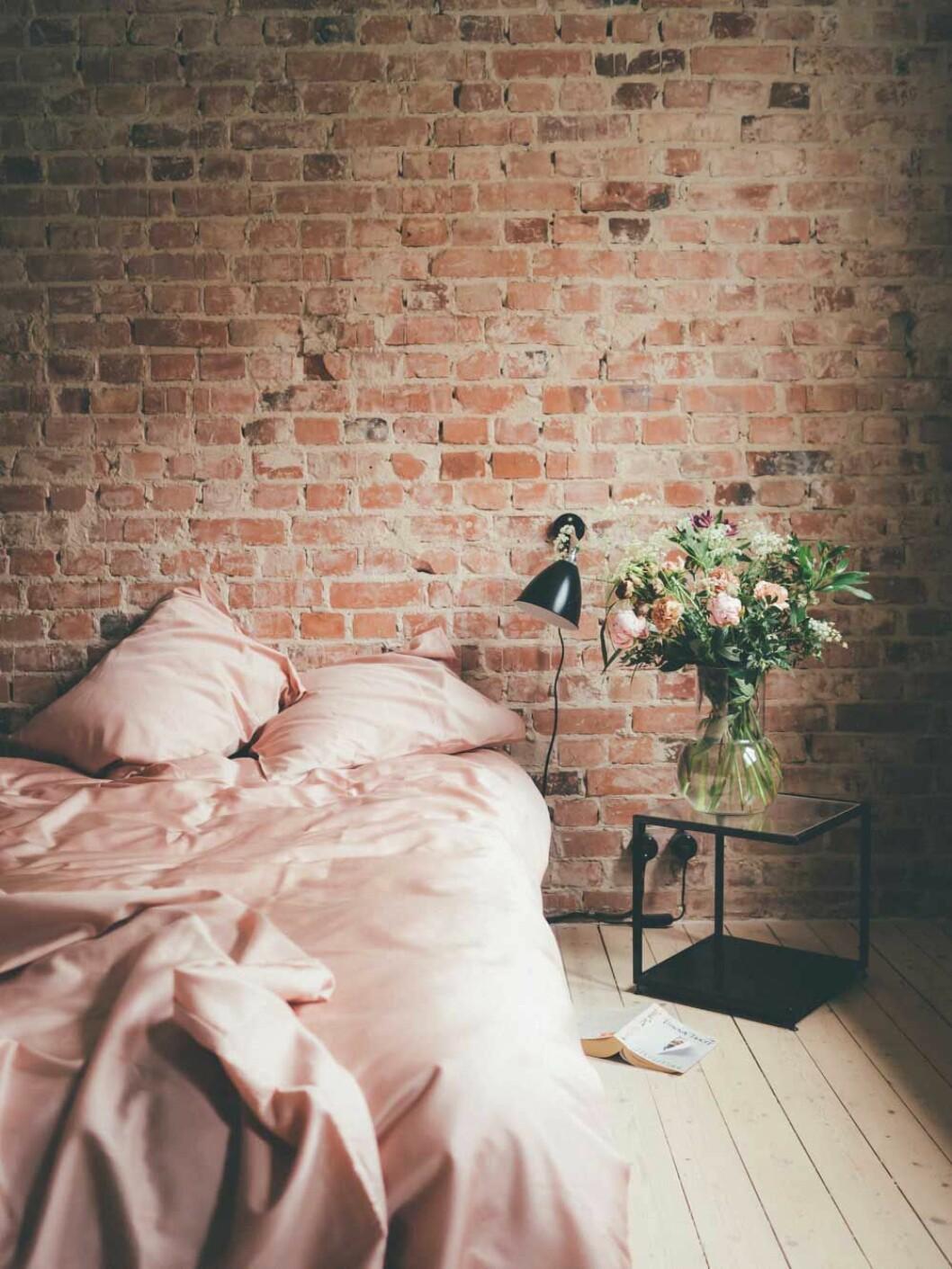 Elin Lannsjös fantastiska sovrum med en fondvägg i tegel