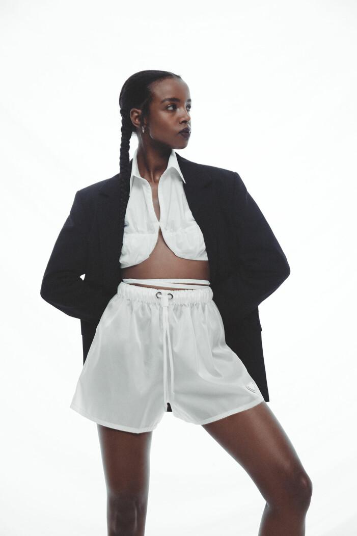 Modellen bär kavaj från Acne Studios, skjorta från Jacquemus/Mytheresa, shorts från Prada/Mytheresa, örhängen från Bottega Veneta.