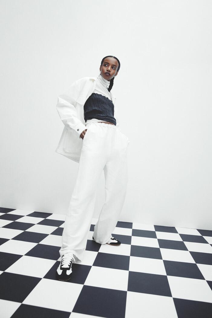 Modellen bär jacka, linne och byxor från Totême, polotröja från COS, skor från Loewe, örhängen från Bottega Veneta.