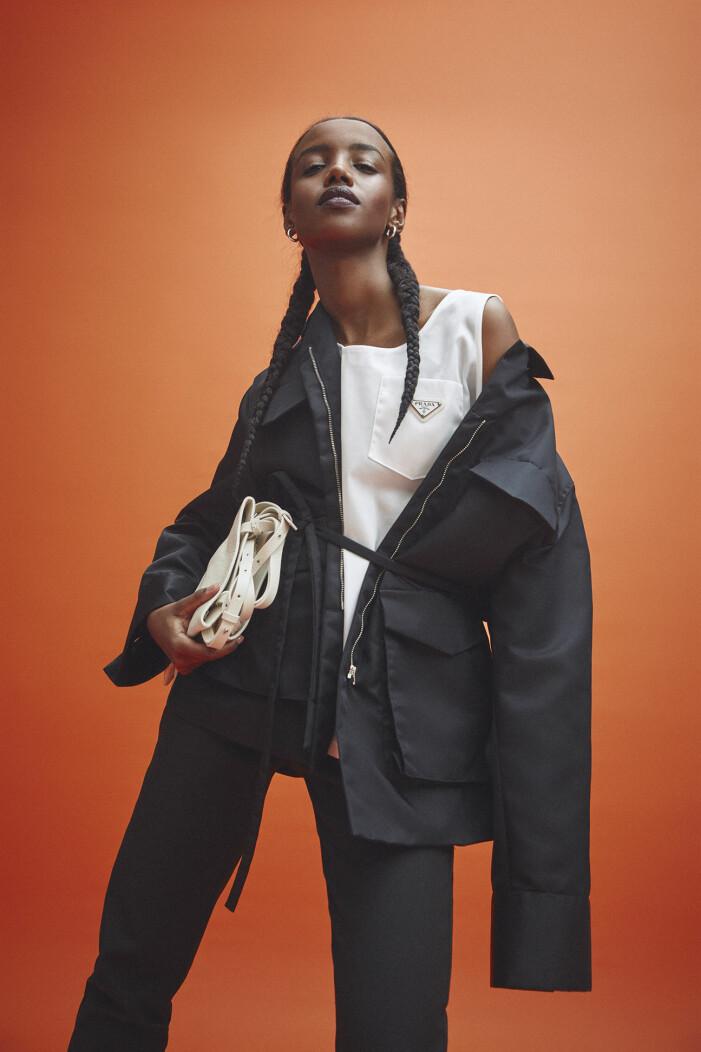 Modellen har på sig jacka och byxa från Totême, linne från Prada/Mytheresa, örhängen från Bottega Veneta.