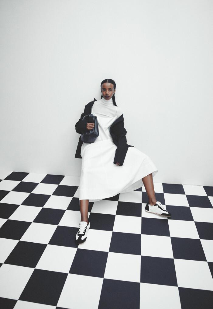 Modellen har på sig kavaj från Acne Studios, klänning från Totême, polotröja och väska från COS, skor från Loewe, örhängen från Bottega Veneta.