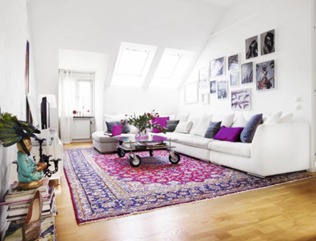 Vitt vardagsrum med lila detaljer hemma hos Rebecca Simonsson.