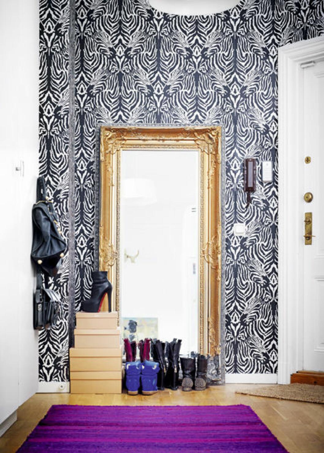 Färgsprakande hall med stor spegel och zebramönstrad tapet