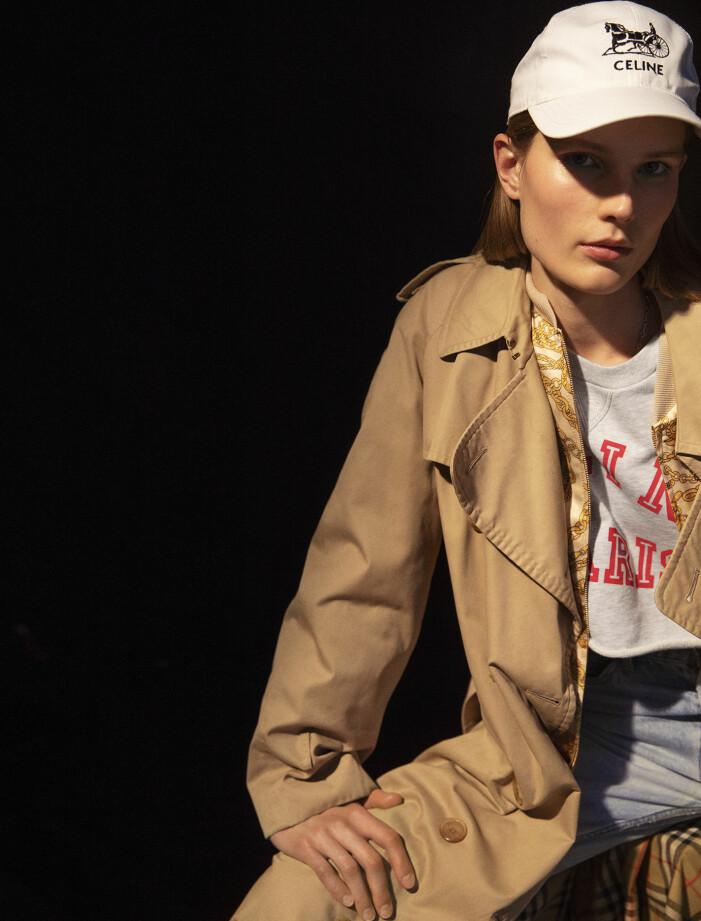 Modellen har på sig trenchcoat från Vestiaire Collective, jacka, tröja, jeans och keps från Celine by Hedi Slimane.