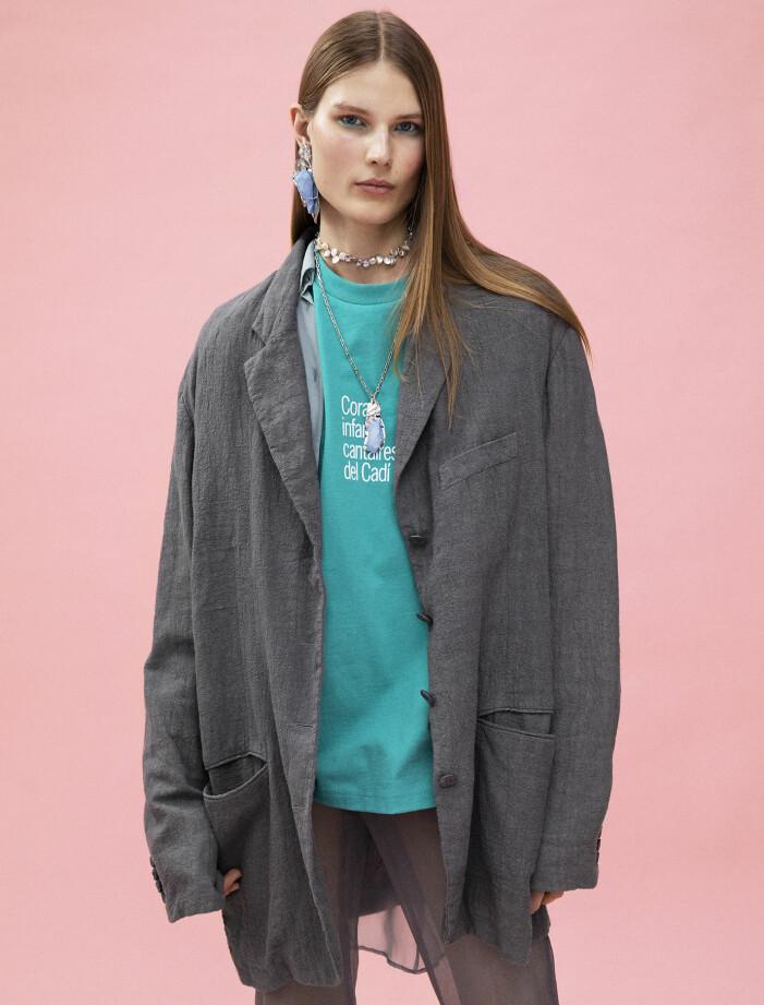 Modellen har på sig kavaj, skjorta, t-shirt, byxor, strumpor, pärlhalsband, kedjehalsband och örhänge från Acne Studios.