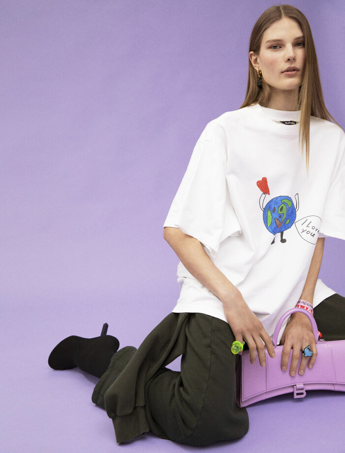 Modellen har på sig T-shirt, overall som byxor, skor, neongrön ring, delfinring, rosa armband, rött armband, örhänge, och väska från Balenciaga.