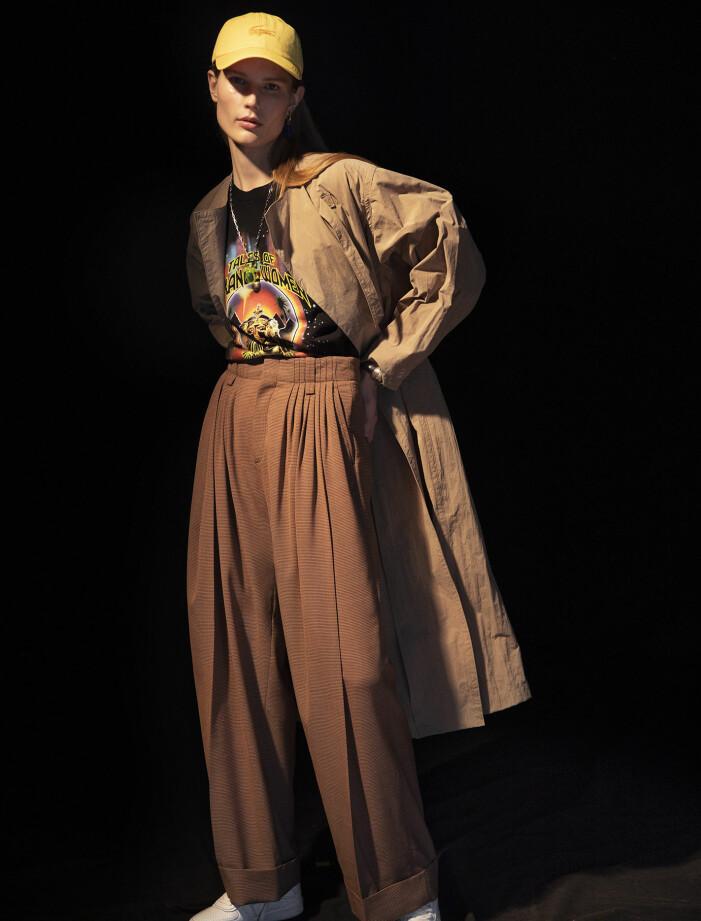 Modellen har på sig trenchcoat från Isabel Marant, T-shirt från Stella McCartney/Mytheresa, byxor från Chloé/Mytheresa, keps från Lacoste, skor från Celine by Hedi Slimane, halsband från Acne Studios, berlock och örhänge från Balenciaga, stelt armband från Chloé.