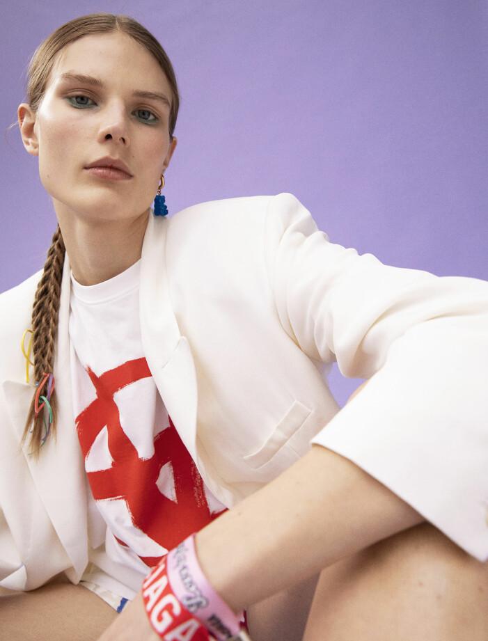Modellen har på sig kavaj och shorts från Isabel Marant, T-shirt från Vetements/Mytheresa, rosa armband, rött armband och örhänge från Balenciaga.
