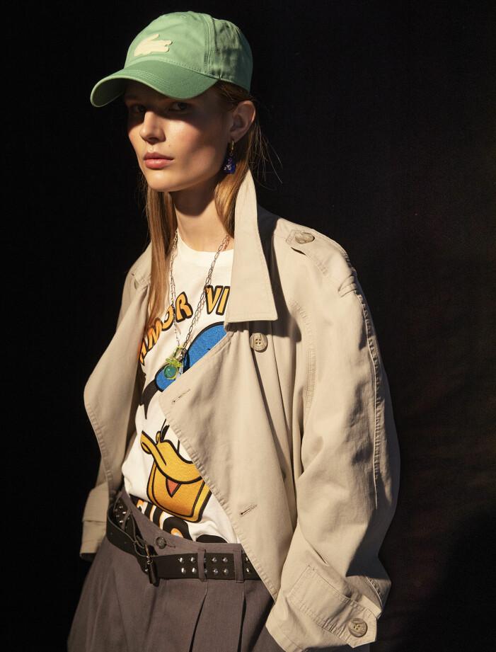 Modellen har på sig trenchcoat och byxor från Beyond Retro, T-shirt från Gucci/Mytheresa, keps från Lacoste, skärp från Shock, halsband och kedjearmband från Acne Studios, berlock, ring, armband och örhänge från Balenciaga.
