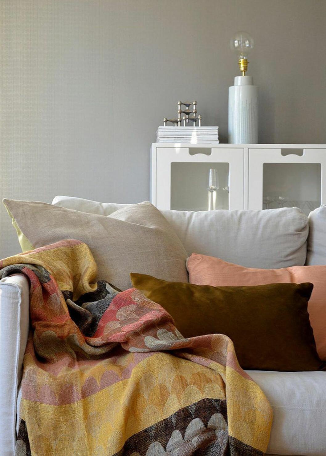 Kuddar och plädar i olika färg och utförande på soffan