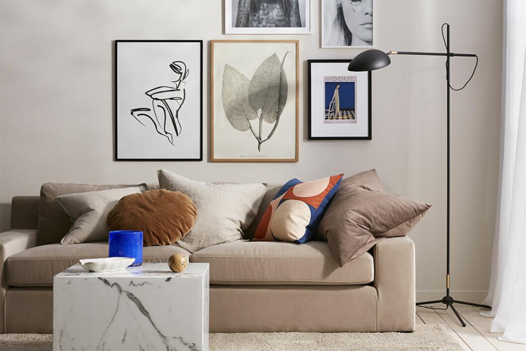 Beige soffa från Ellos Home och posters samt koboltblå kruka