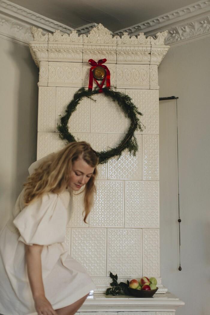 Elsa Billgren hanger upp krans av granris med rott band