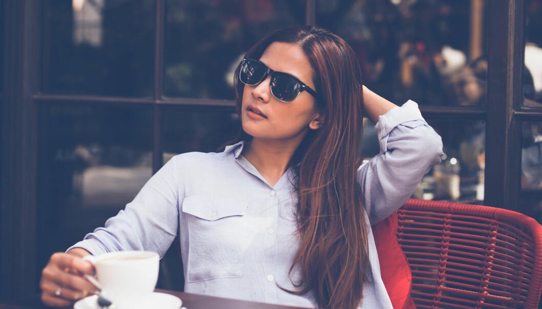 Kvinna som dricker kaffe på café