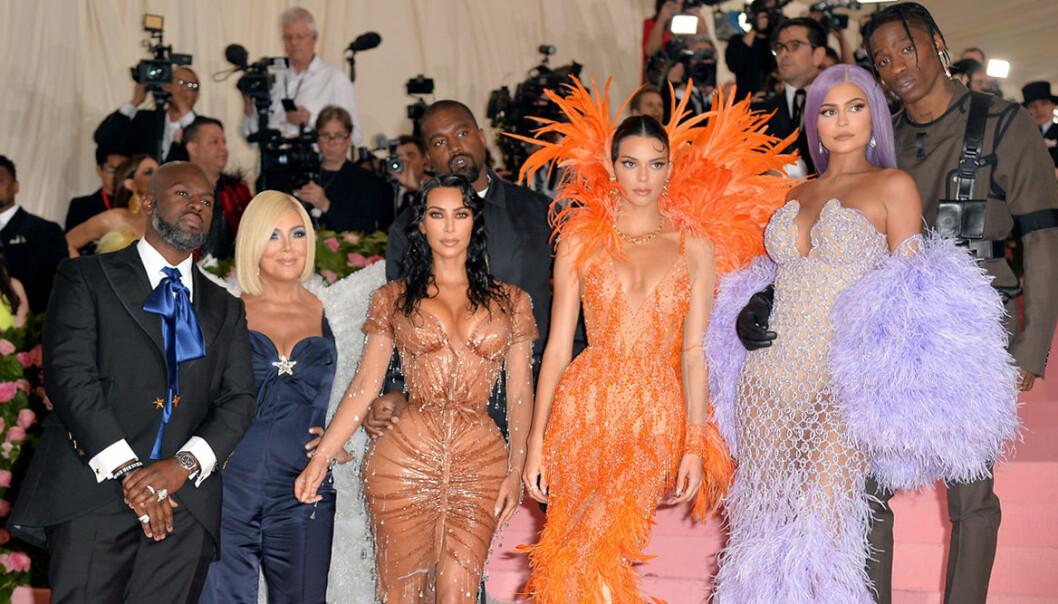 Familjen Kardashian/Jenner står i en trapp och blir fotade av massa paparazzifotografer
