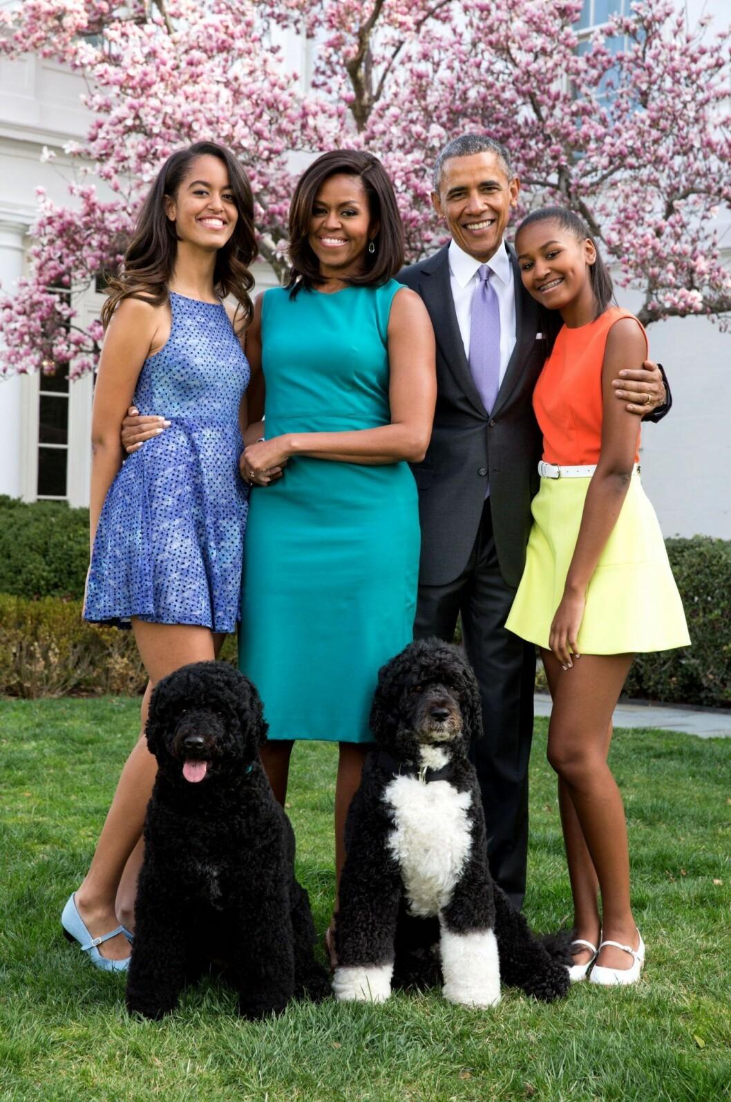 Michelle, Malia, Barack och Sasha Obama. står i trädgården i färgglada kläder och med två hundar framför sig