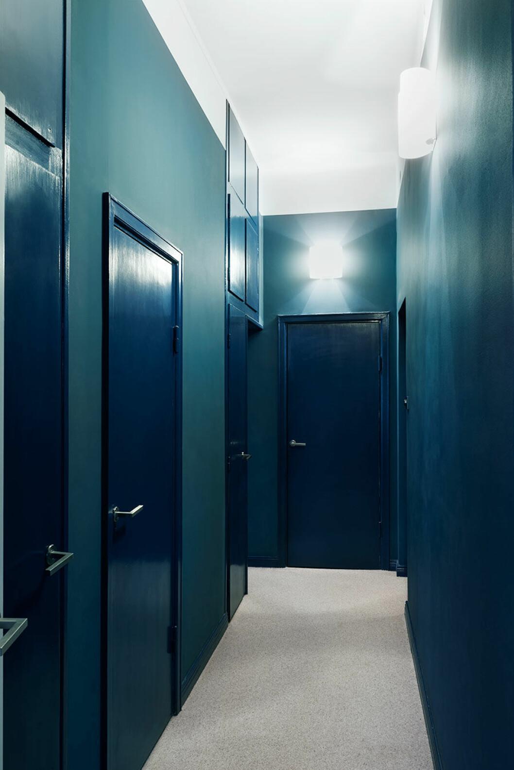 """Korridoren med klädkammaren i ena änden och de tre sovrummen i fil längs med ytterväggen. Den avskilda privata känslan förstärks av den omboande heltäckningsmattan och färgvalen. Väggarna är målade i en helmatt blå nyans som står i effektfull kontrast mot dörrar och listers högblanka finish. """"Jag ville egentligen ha ännu mer färg"""", säger Clara."""