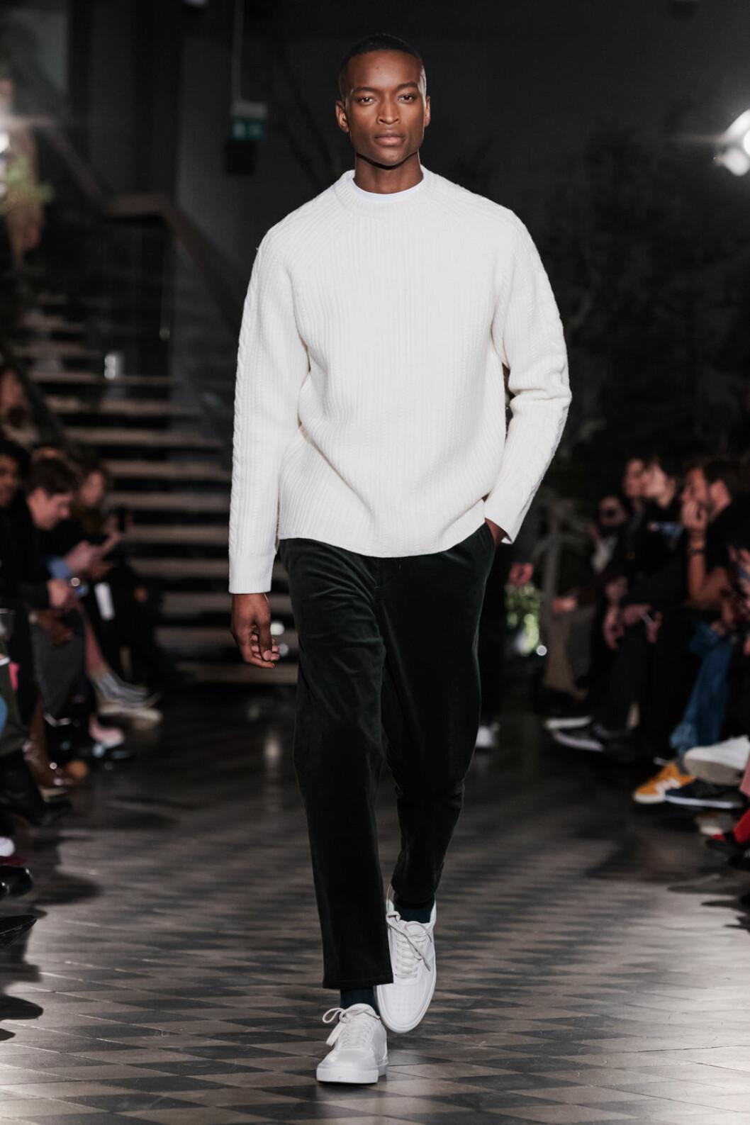 Filippa K AW 18, man i vit stickad tröja och svarta byxor.