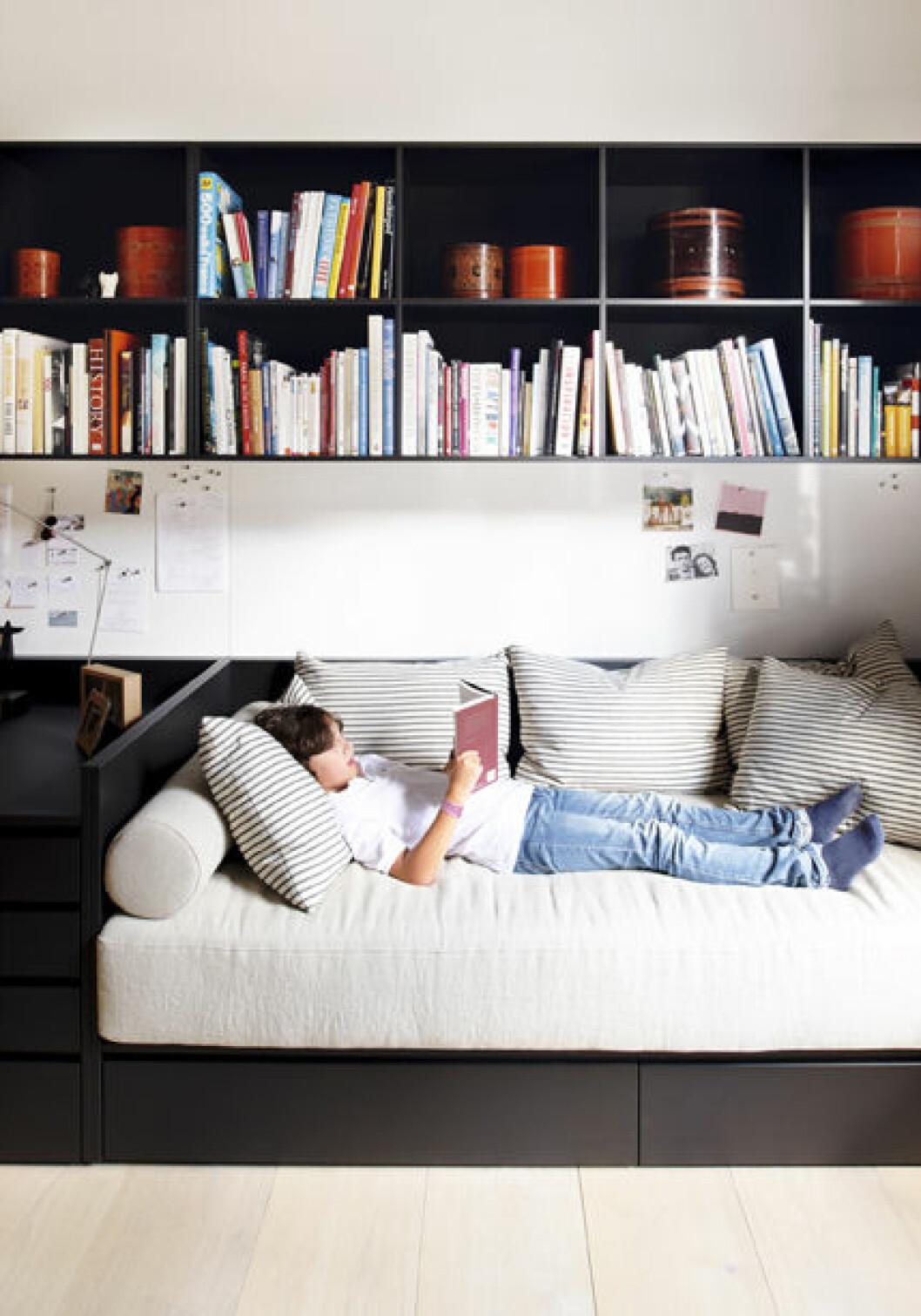 Filippa Knutssons son läser en bok i hemma i soffan med bokhylla ovanför.