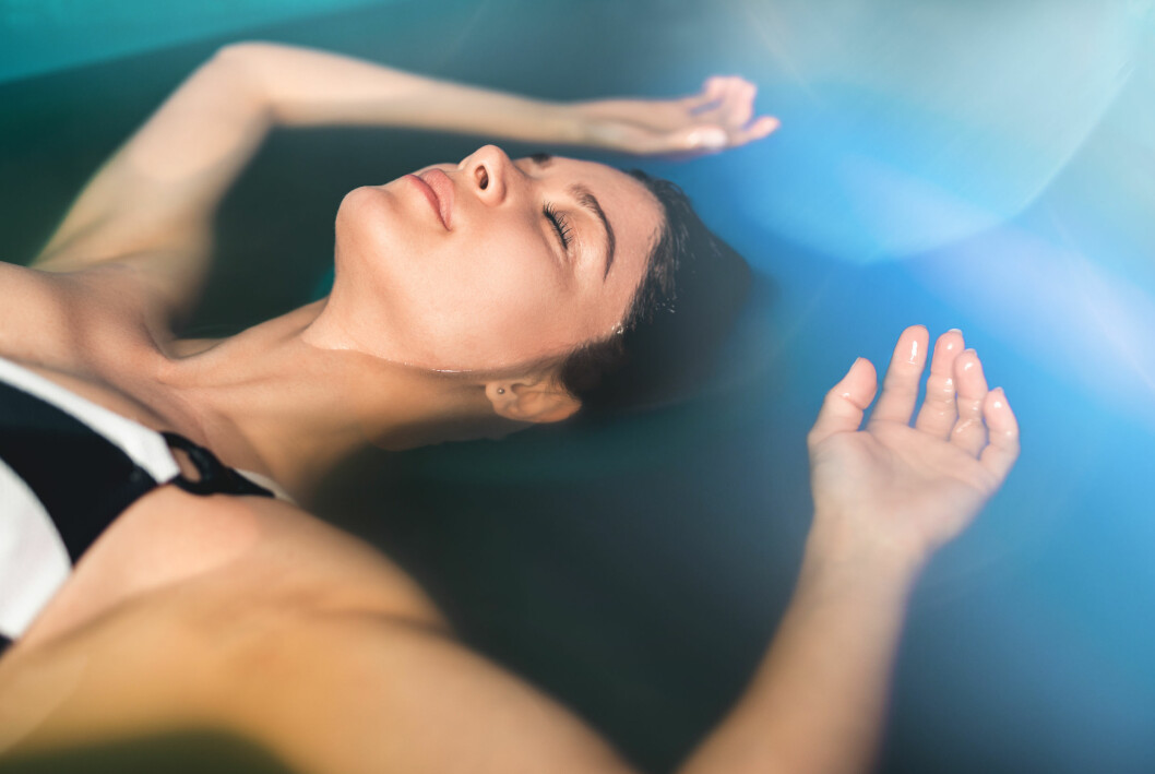 Kvinna som flyter i vatten - floating