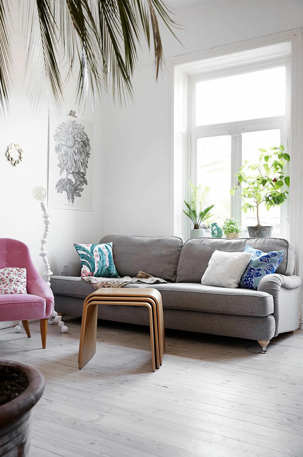 Grå soffa och ljusrosa fåtölj i vardagsrummet