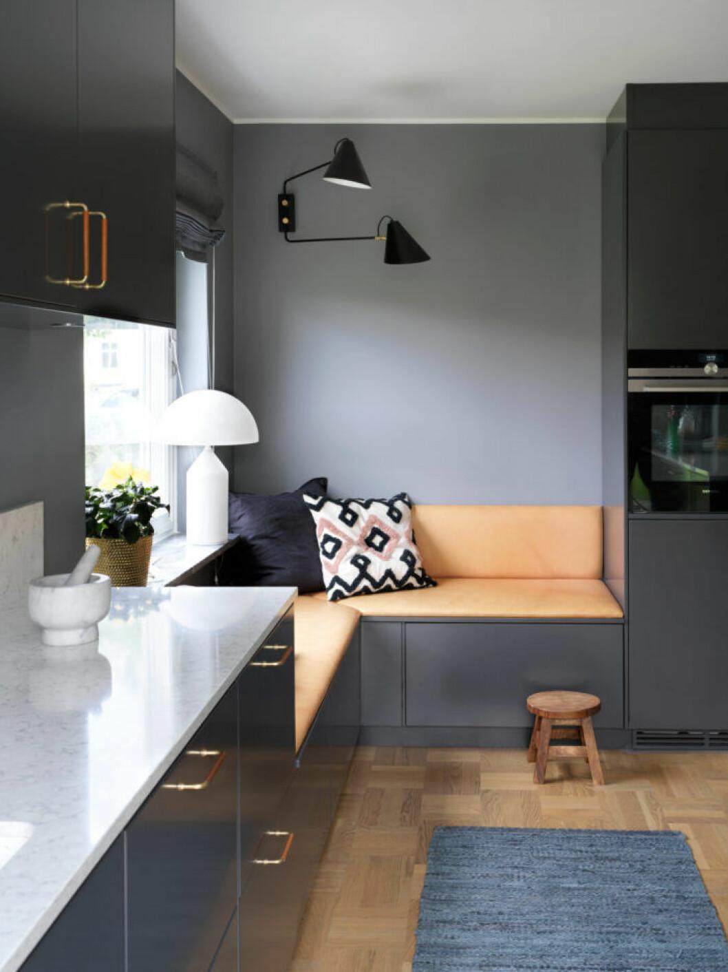 Grått platsbyggt kök med orangea detaljer hos Frida Fahrman