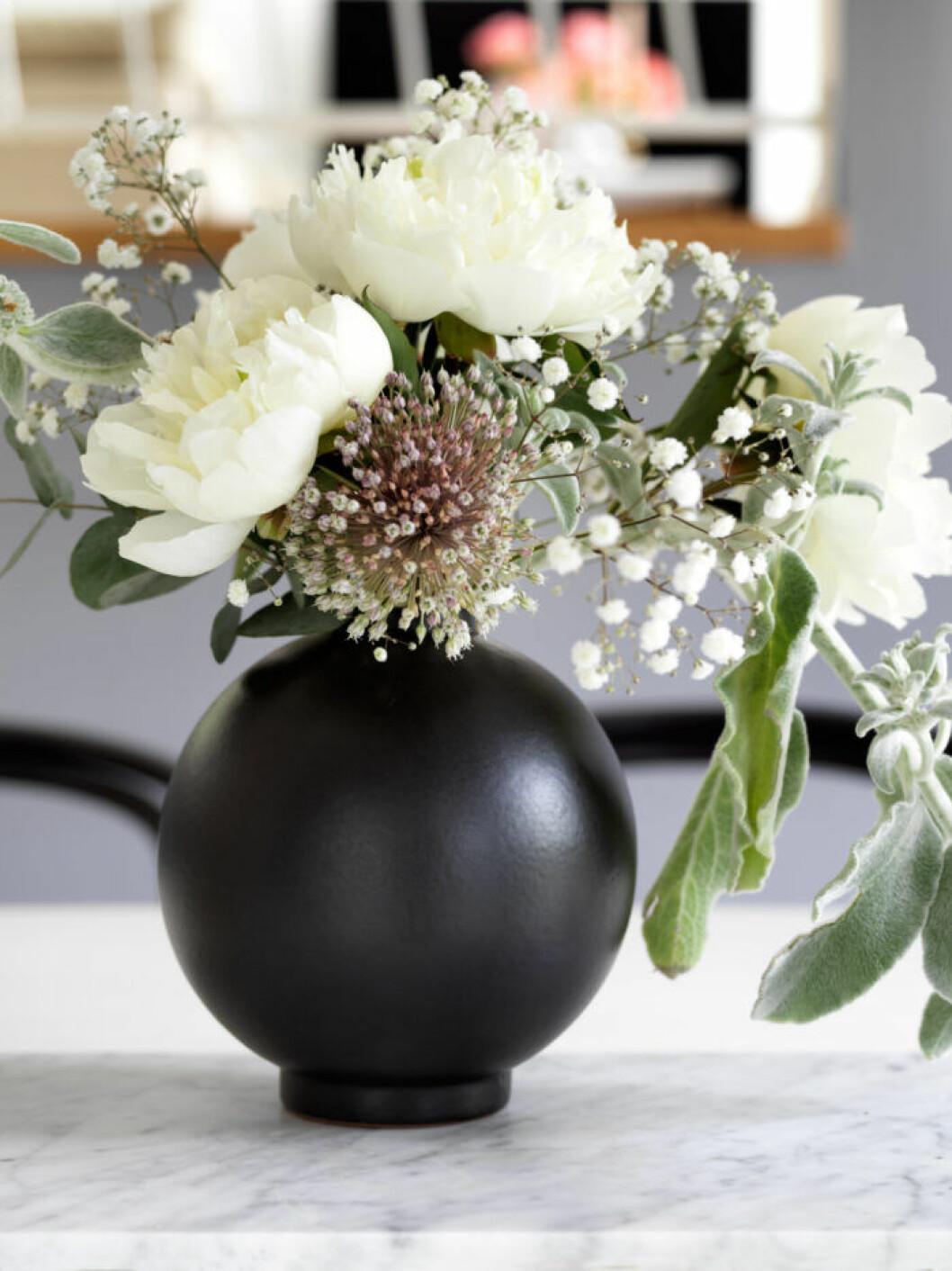 Svart vas med säsongens blommor hos Frida Fahrman