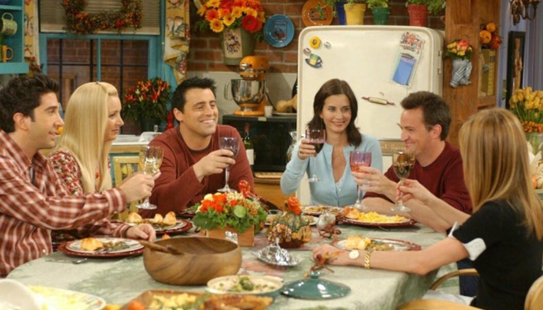 Gänget från vänner sitter runt ett bord och skålar