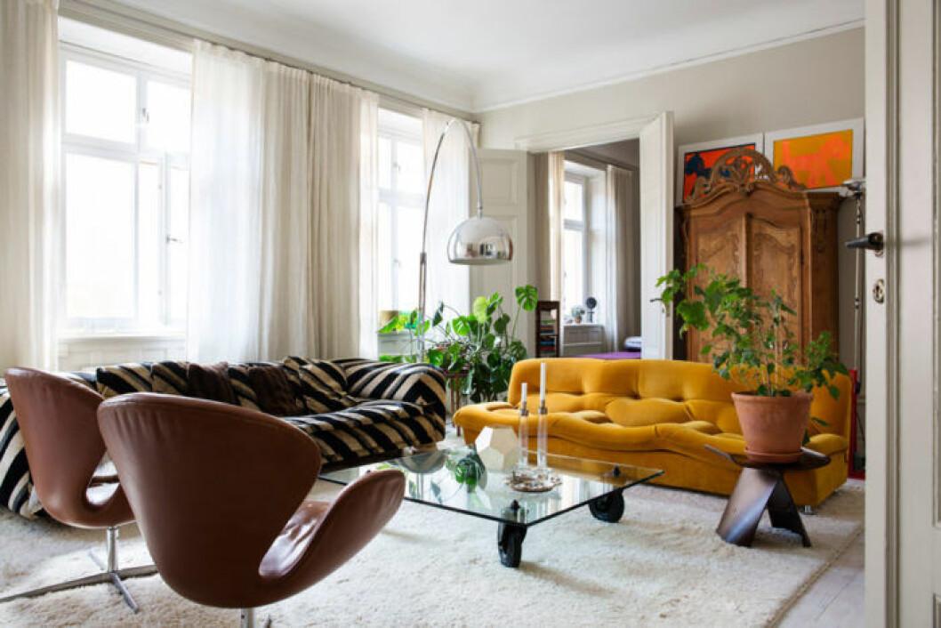 Vardagsrummet går i naturnära toner med en senapsgul soffa och bruna fåtöljer