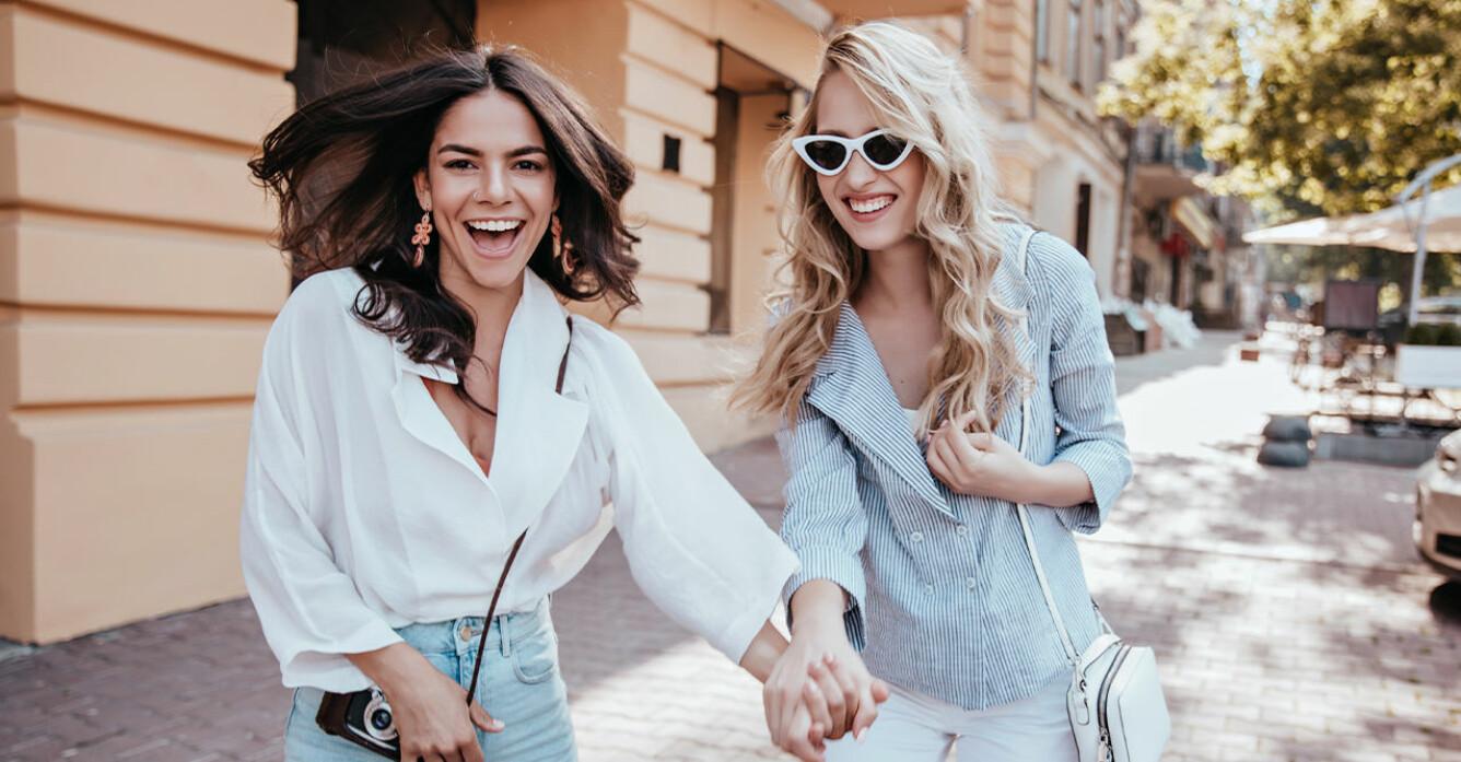 två glada tjejer håller varandra i handen