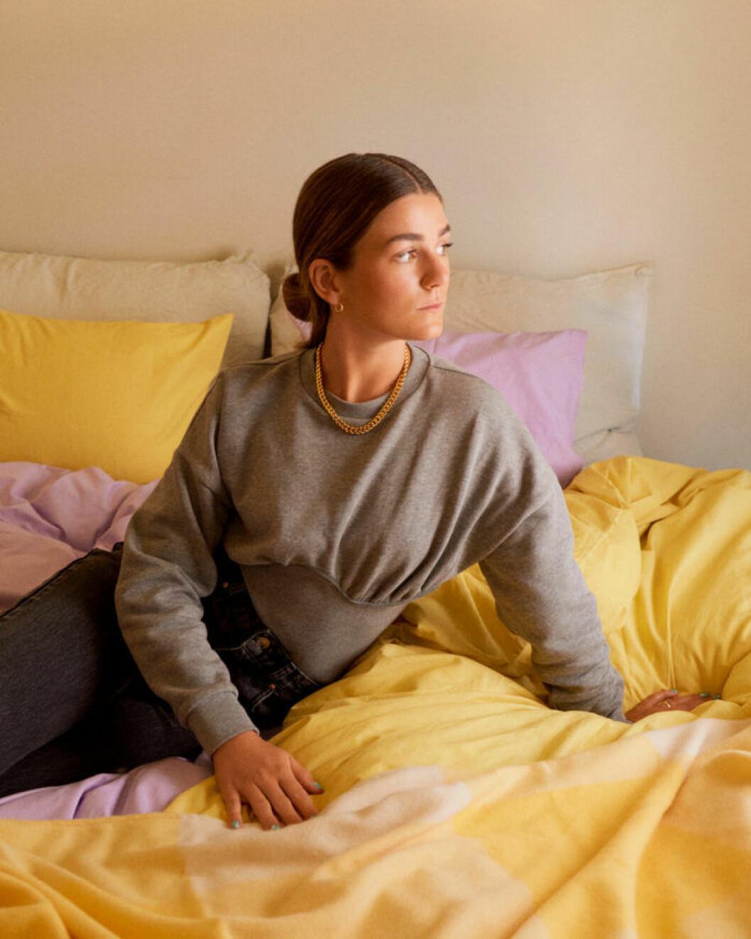 Linn Eklund visar Gina Tricots nya bäddset i gult och rosa.
