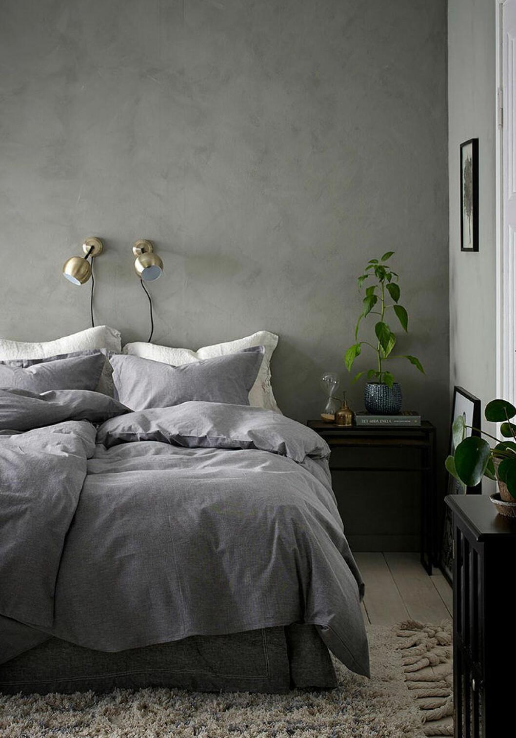 Gråa väggar i sovrummet, där även sängkläderna går i samma nyans