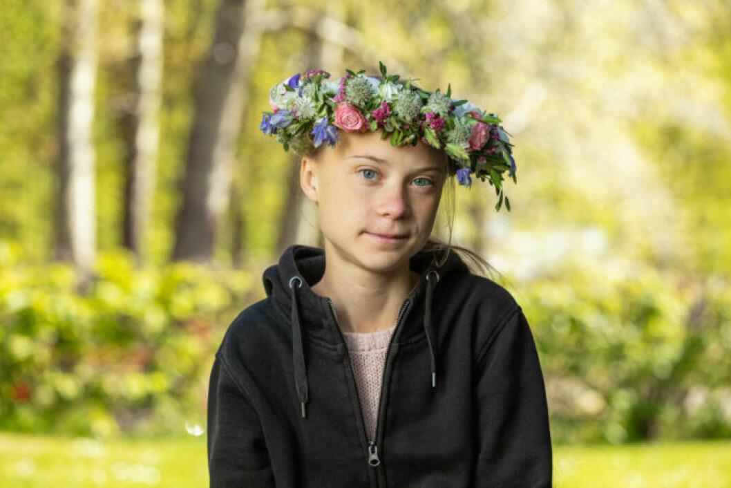 Greta Thunberg i svart munkjacka och blomsterkrans i håret