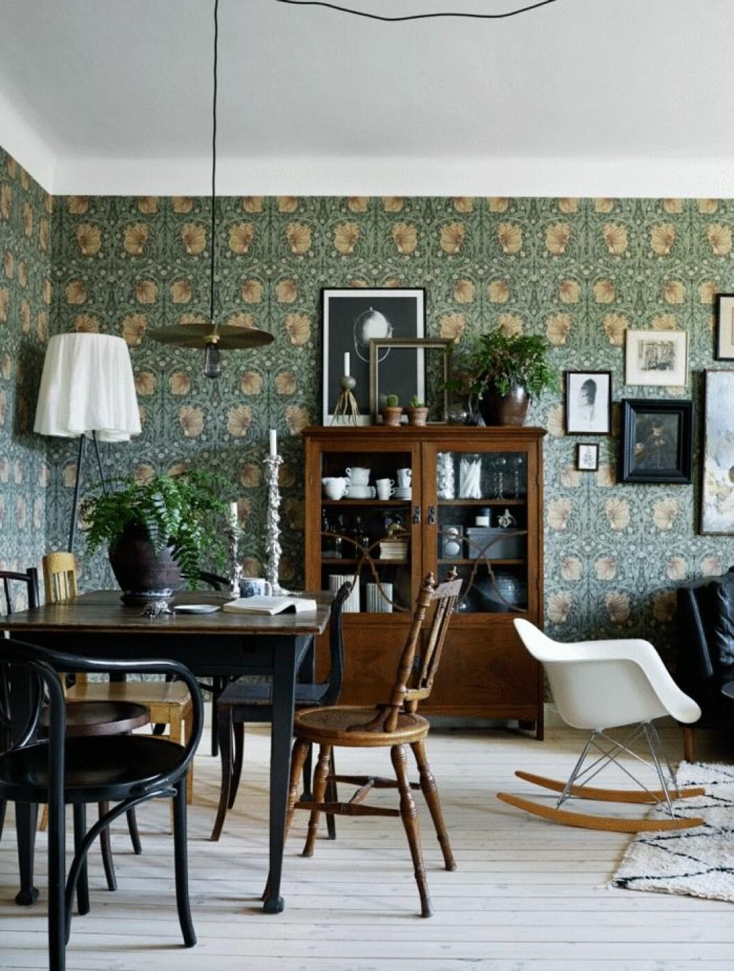 Vardagsrum med färgstark tapet i härligt mörkgrönt mönster