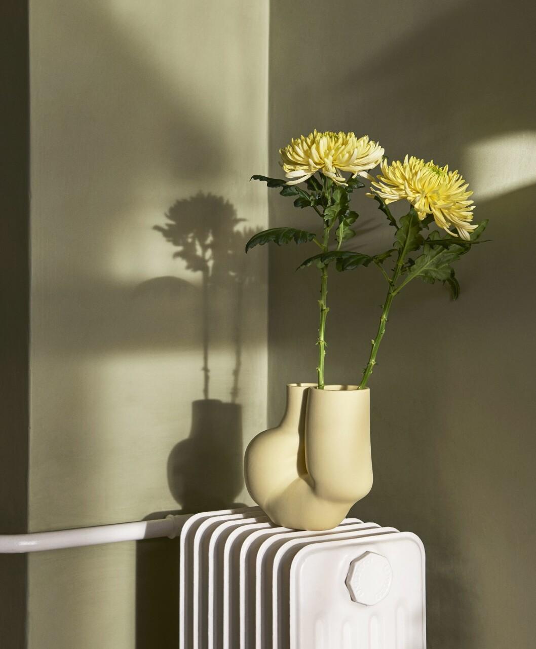 gul vas med gula blommor i