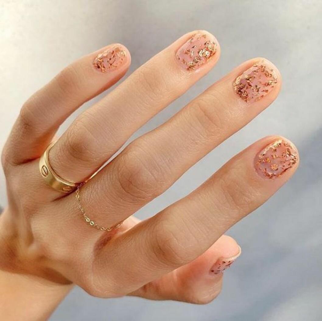 En bild på en nagelmanikyr i guldglitter.