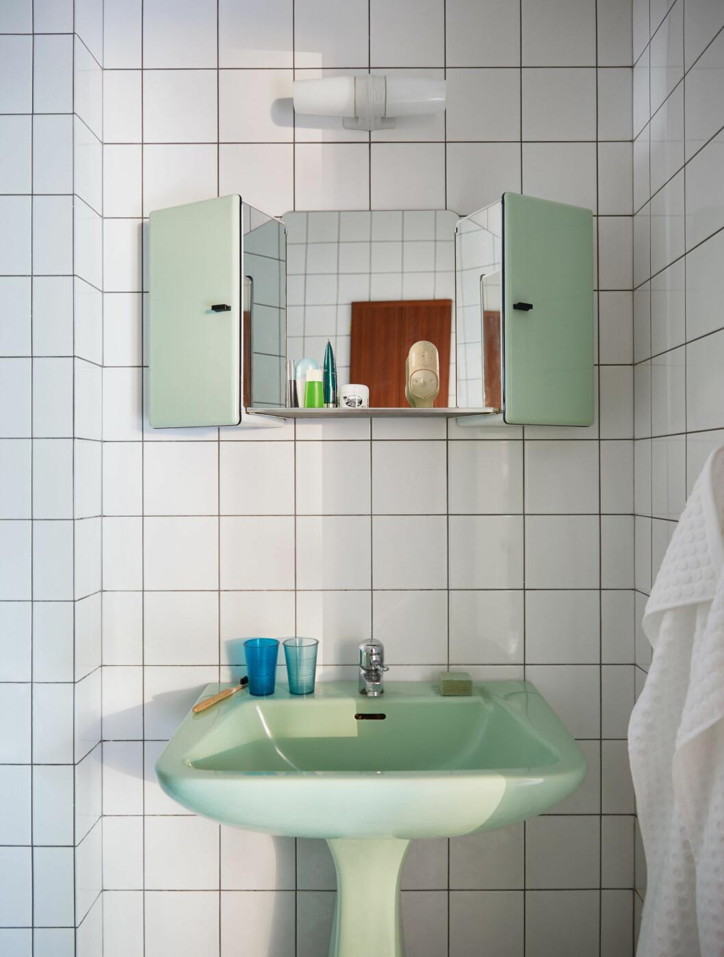 Badrum i vitt kakel och både mintgrönt handfat och förvaring i 70-talsanda