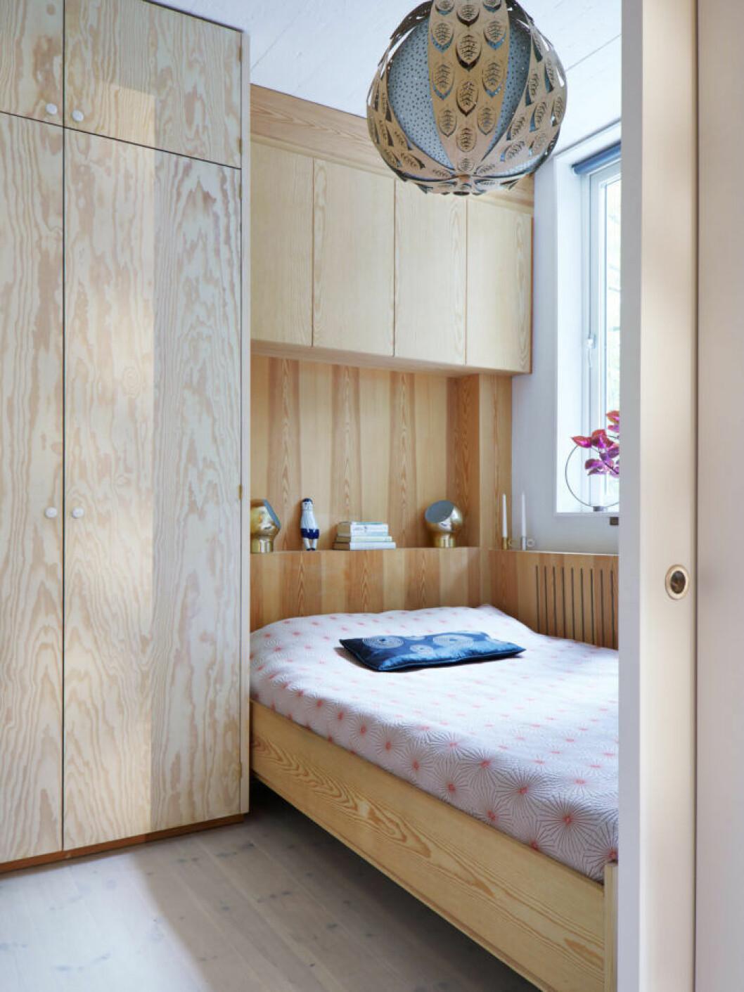 Sovrummet går i ljust trä med platsbyggd förvaring både bredvid och över sängen