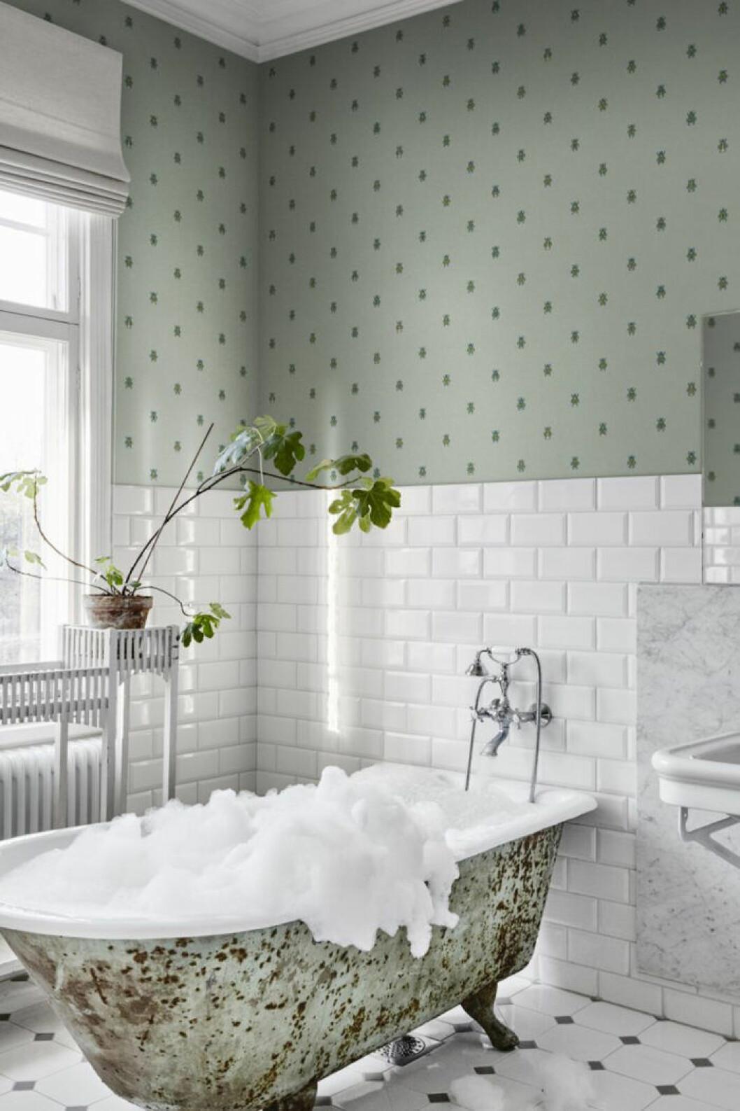 halvkaklat badrum med badkar och tapet